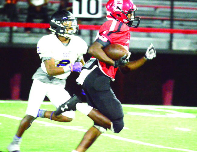 PULLING AWAY — Big Red's Taveon Montgomery rushes away from a USO defender Friday at Harding Stadium (Photo by Michael D. McElwain).