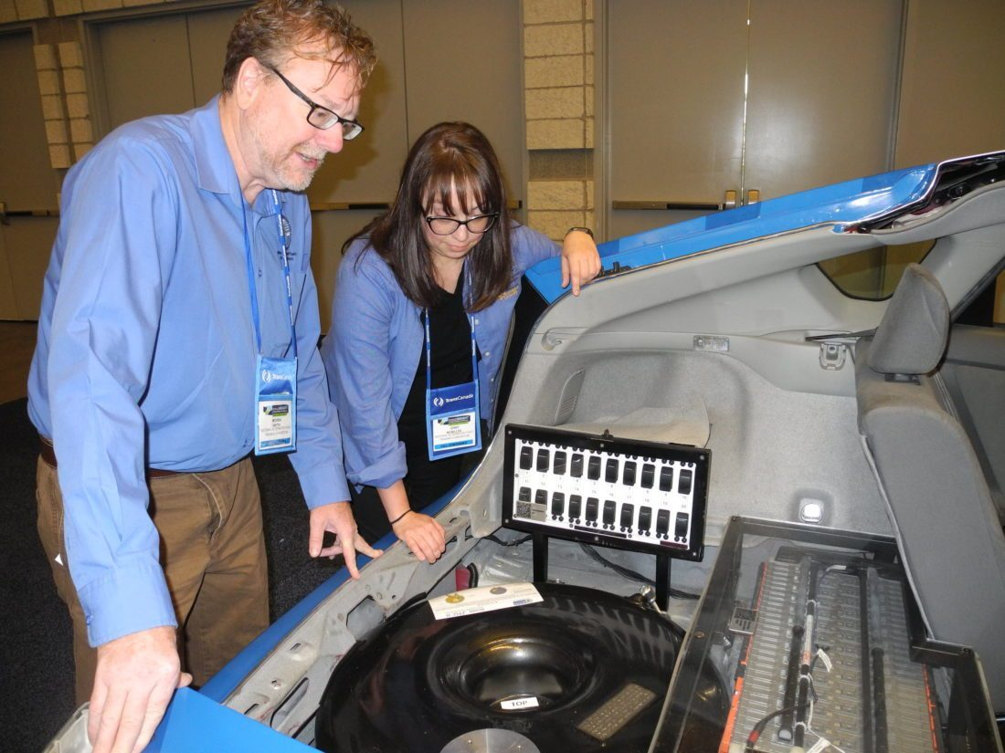 HYBRID TECHNOLOGY — West Virginia University researchers inspect a hybrid vehicle, that can be fitted to run on natural gas, propane or other alternative fuels, Thursday during the Shale Insight conference in Pittsburgh. The researchers are Virginia McMillen, communications specialist of the National Alternative Fuels Training Consortium, and Michael Smyth, who serves as the director of the group. -- Casey Junkins