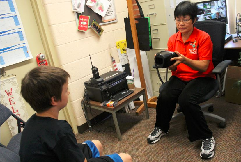 SCREENING TIME —  Richmond Lions Club member Sahn Huscroft performs a vision screening on a fifth-grade pupil at John Gregg Elementary in Bergholz recently as part of the sight-saving organization's annual project. The club provides free screenings in Jefferson County schools and had stops at Edison High School and the Jefferson County Joint Vocational School also on its agenda. The club hopes to extend its reach to other age demographics in the community. -- Contributed