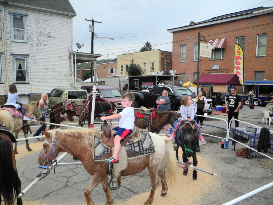 Jackson Temple, 4-year-old grandson of Robin Snyder of Wellsburg; and Paisley Willhoft, 4-year-old daughter of Caity Deevers, enjoyed a pony ride during the Wellsburg Applefest Friday. The festival continues today with a variety of food, craft and other vendors and musical entertainment from 11 a.m. to 6 p.m. -- Warren Scott