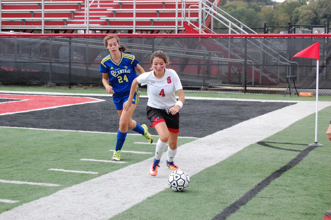 PURSUIT — Big Red's Jadyn Bennett tracks down the ball with Catholic Central's Liz Bolster pursuing Saturday at Harding Stadium. (Photo by Andrew Grimm)