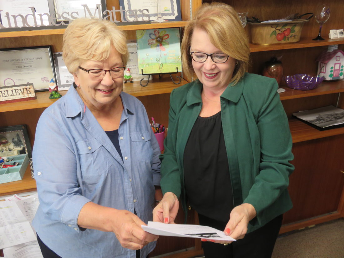 HELPINGELDERORPHANS — Judy Owings, right, director of the Prime Time Senior Center, and Stephanie Wendell look over particulars about the new Friends Helping Friends support group Wendell leads at the Prime Time Senior Center on Lovers Lane, Steubenville, on the third Monday of the month, beginning at 1 p.m. -- Janice Kiaski