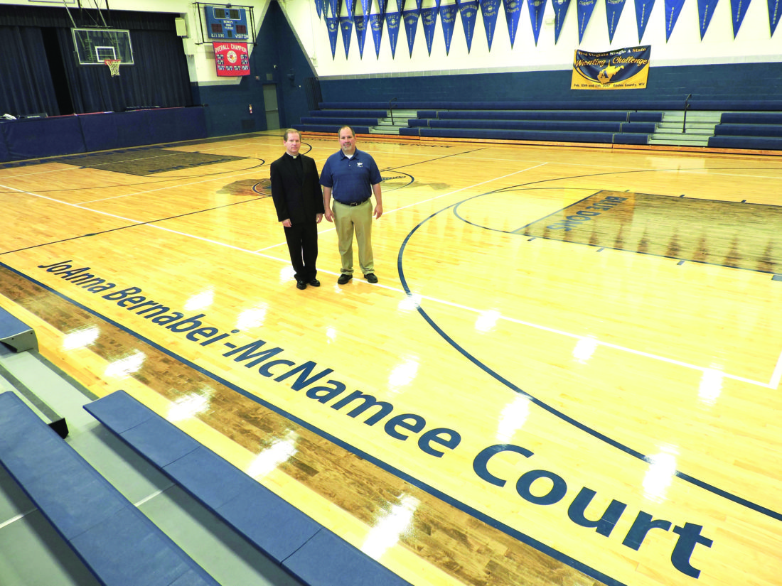 NEW NAME — The Rev. Dennis R. Schuelkens Jr.  and Jamie Lesho, principal at Weirton Madonna High School, stand on the recently re-named Joanna Bernabei-McNamee Court at the high school. The court was named in honor of McNamee, a 1993 graduate, also commemorating the 25th anniversary of the girls basketball state championship won by the school in 1992. (Photo by Craig Howell)