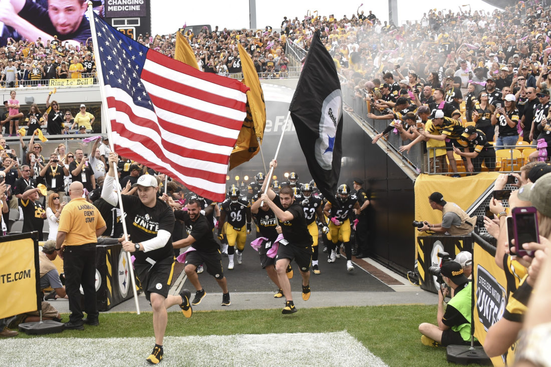 BEHIND THE FLAG — Flag bearers lead the Pittsburgh Steelers onto Heinz Field Sunday before their game with the Jacksonville Jaguars. The Chester American Legion won't be putting NFL games on the post TVs as a result of players' protests during the national anthem this season. -- Associated Press