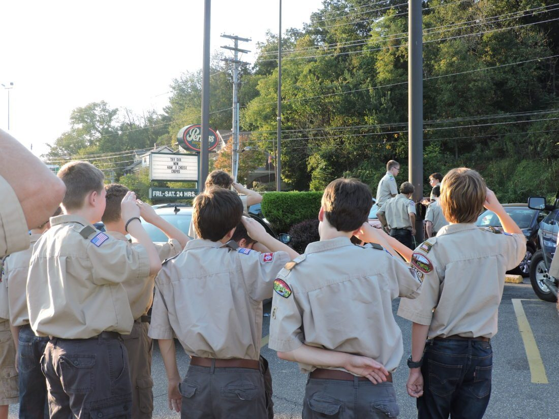 FLAG RESPECT — Troop 6 Boy Scouts from Vance Church in Wheeling salute the flag. Scout leaders in the Wheeling area say they welcome the decision to accept girls. -- Heather Ziegler