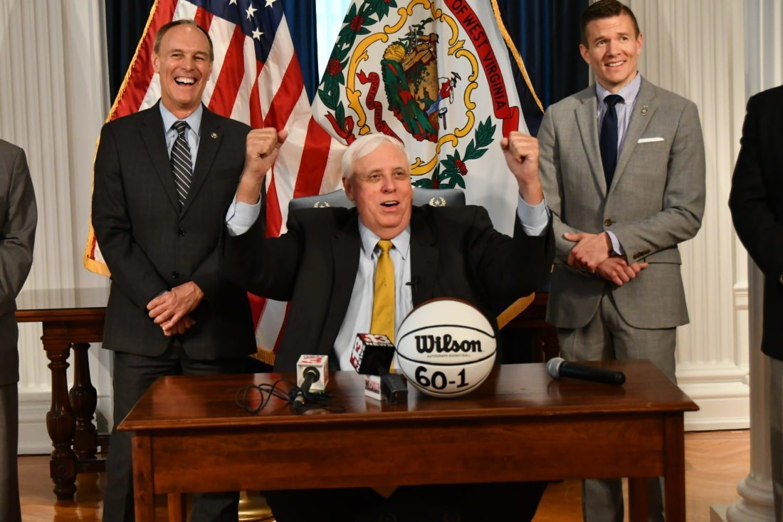 LETS OUT A CHEER — West Virginia Gov. Jim Justice cheers during a press conference Wednesday morning in Charleston, flanked by state Senate President Mitch Carmichael, R-Jackson, left, and Senate Majority Whip Ryan Weld, R-Brooke.	-- Contributed