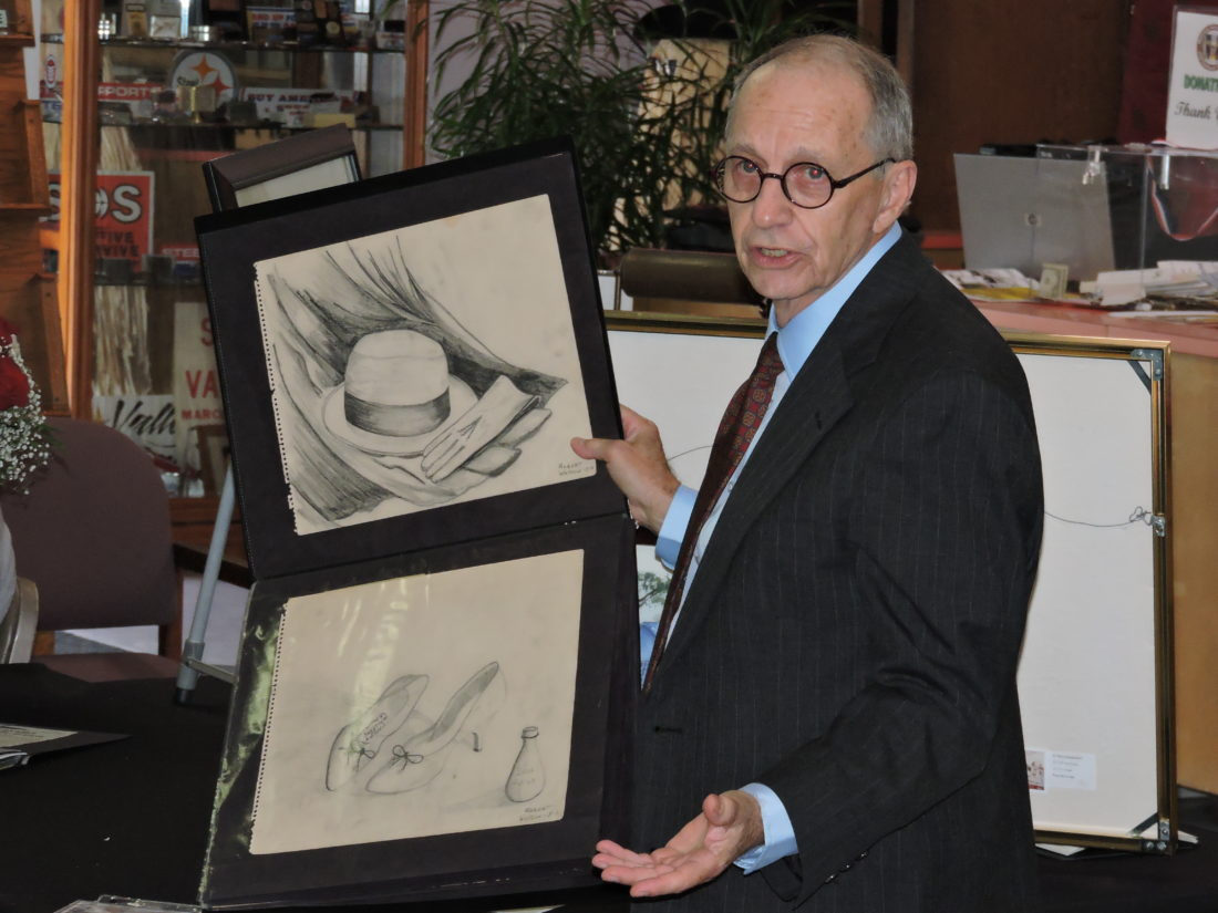 ARTIST OF THE YEAR — Robert L. Watson Jr., the featured artist of this year's Robert Haworth Memorial Art Exhibition, shows some of the sketches he drew while a student of Haworth's at Weir High School. The ninth-annual exhibition was held Saturday at the Weirton Area Museum and Cultural Center. -- Craig Howell