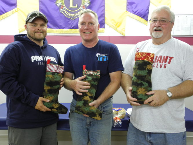 STOCKINGS FILLED — Christmas stockings for Boatsies Boxes were filled by the Brilliant Lions Club. The stockings were made in a camouflage fabric with Christmas decorations on the top by Rita Boyd of Brilliant as part of a project chaired by Esther McCoy and Kevin Huggans With some of the stockings are, from left, Roger Herbert, Buckeye Local football coach, who was a guest; Huggans; and Ralph Nickoson, president. -- Contributed