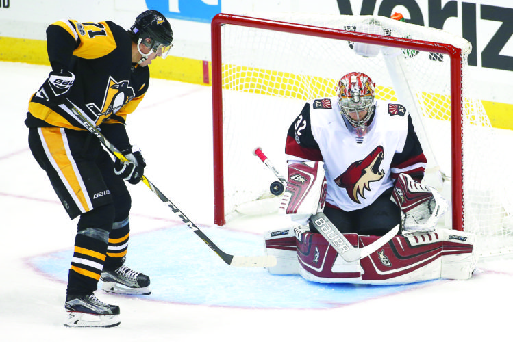 DEFLECTION — Pittsburgh Penguins' Evgeni Malkin deflects a rebound past Arizona Coyotes goalie Antti Raanta for a goal during the first period on Tuesday. (AP Photo)