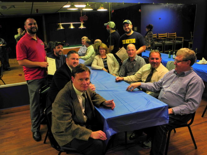NEW PLACE TO EAT — Brian Tennant, standing left, and Kyle Hood, standing right, offer menus to several members of the Wellsburg Chamber of Commerce and guests during a business after hours held at their new business, the Northend Lounge. Located at 2239 Charles St., the lounge offers wings in 15 flavors, several sandwiches and a full-service bar with a pleasant atmosphere. Its customers during the Business After Hours included, clockwise from left, David George, Chamber President David Klick, Rowdy Rush, Chamber Coordinator Jacie Ridgely, Harry Sanford, Frank Johnson and Richard Ferguson. Warren Scott