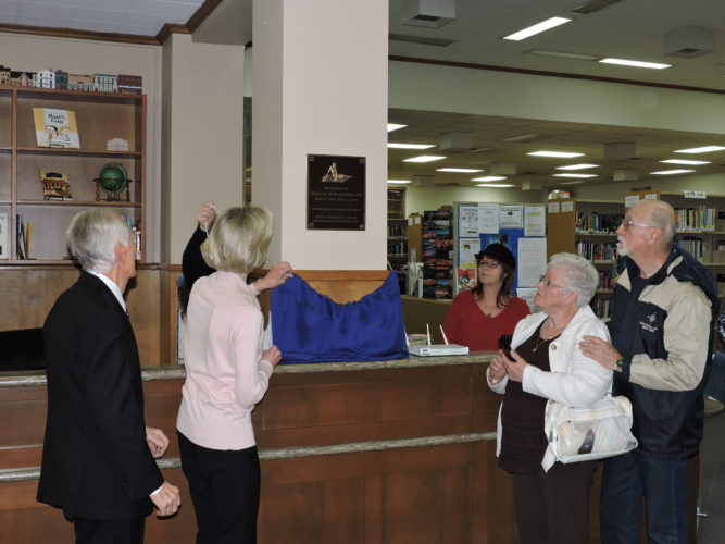 During Thursday's event at the Mary H. Weir Public Library, a plaque dedicated in memory of Julia N. Schaltenbrand was unveiled in the library's lobby. Assisting with the unveiling are, from left, library board President Joe Evano and board member Karen Gould; John Semerakis, Schaltenbrand's brother, and Anna Semerakis. -- Craig Howell