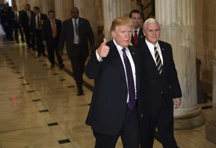 TAX PROPOSAL — President Donald Trump gives a thumbs up while walking with Vice President Mike Pence as he departs Capitol Hill in Washington, Thursday. Trump urged House Republicans Thursday to approve a near $1.5 trillion tax overhaul as the party prepared to drive the measure through the House. Across the Capitol, Democrats pointed to new numbers showing the Senate version of the plan would boost taxes on lower and middle-income Americans. -- Associated Press