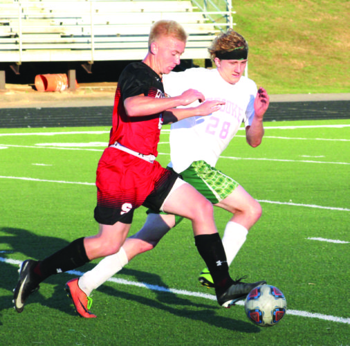 RACING BY — Steubenville's Ryan Delelles races by Brooke's Gage Barnhart on Oct. 3 in Brooke. (Photo by Joe Catullo)