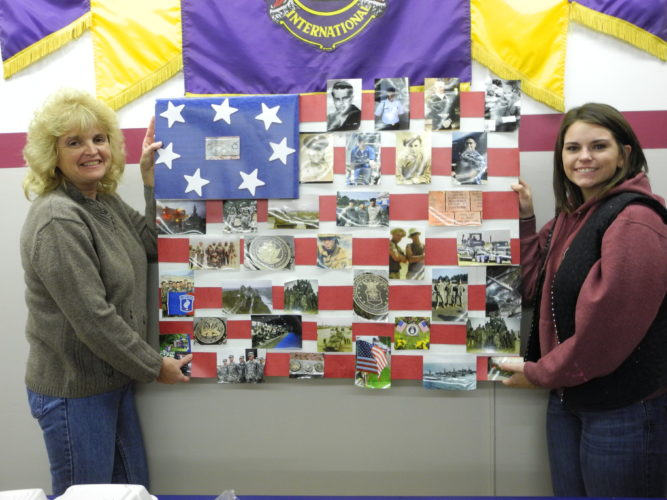 MILITARY THEME — The Backwoods 4-H Club designed a military theme for its booth at the Jefferson County Fair in the 4-H Building. Head adviser Carol Ramsey, left, and Paxton Shields, a 4-H member who will be a Cloverbud adviser in 2018, brought a flag board decorated with military families of 4-H members to the Brilliant Lions Club and spoke about the project. They gave club members a toy plastic soldier as a reminder to pray for the military serving abroad. -- Contributed