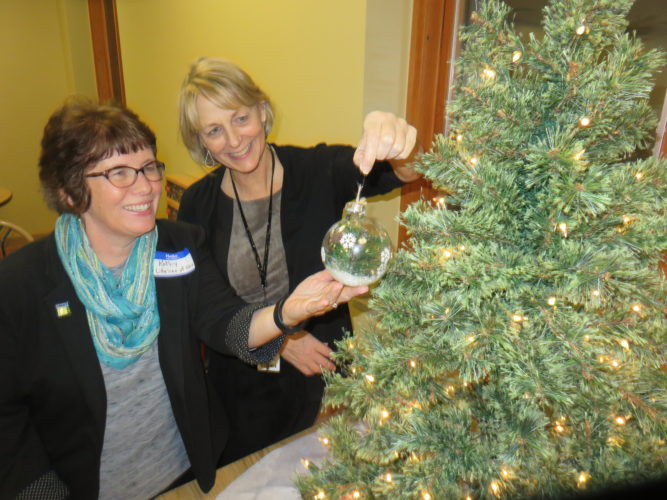 "FINDING JUST THE RIGHT SPOT — Kathy Warhola, left, regional hospital development coordinator for Lifeline of Ohio, and Barb Banfield, Trinity Health System director of nursing, check out one of many bulbs to adorn a Christmas tree in honor of ""the heroes of organ, eye and tissue donation."" Trinity Medical Center West, in conjunction with Lifeline of Ohio, the organ and tissue recovery agency that works with Trinity Health System, held a first-time Gift of Life  event Wednesday where transplant recipients and donor families could gather informally for a bittersweet celebration that included making ornaments in honor of the donors.  -- Janice Kiaski"