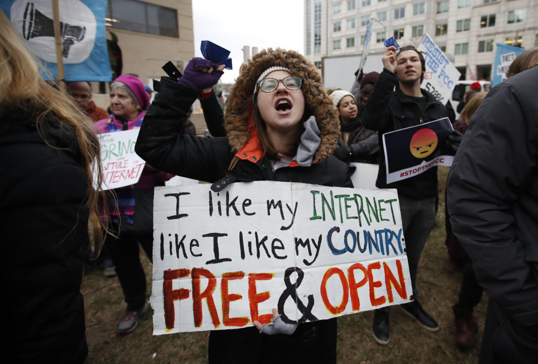 "FCC PROTEST — Diane Tepfer holds a sign with an image of Federal Communications Commission Chairman Ajit Pai as the ""Grinch who Stole the Internet"" as she protests near the FCC, in Washington, Thursday. The FCC voted to eliminate net-neutrality protections for the internet. -- Associated Press"