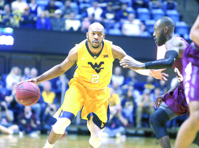 DRIVING DOWN — West Virginia guard Jevon Carter drives up court while being defended by Fordham guard Perris Hicks during the second half on Saturday in Morgantown. (AP Photo)