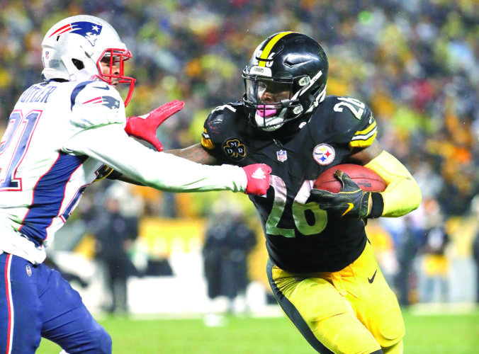 STIFF ARMING — Pittsburgh Steelers running back Le'Veon Bell runs against the New England Patriots on Sunday at Heinz Field in Pittsburgh. (AP Photo)