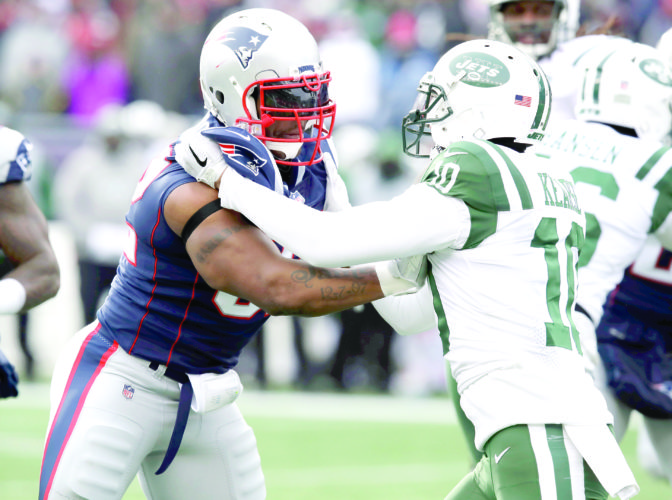 MAKING AN IMPACT — New England Patriots linebacker James Harrison tries to fight through a block by New York Jets wide receiver Jermaine Kearse during the first half on Dec. 31 in Foxborough, Mass. (AP Photo)