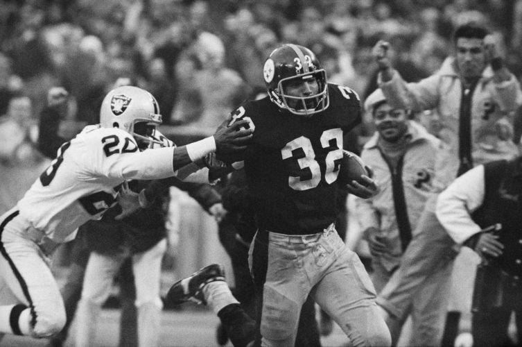 IMMACULATE RECEPTION — Franco Harris eludes a tackle by Jimmy Warren of the Raiders on a 42-yard run to score the winning touchdown in a Dec. 23, 1972, AFC playoff game at Three Rivers Stadium. The run and score came after Harris made his famous catch off of a deflected ball. -- Associated Press