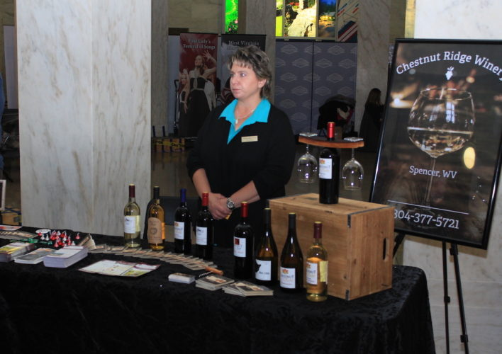 TOURISM DAY — Teresa Holcomb of Chestnut Ridge Winery in Spencer works a booth at Tourism Day at the West Virginia Legislature. -- West Virginia Press Association