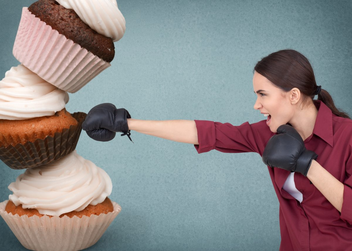 young woman punching giant cupcakes