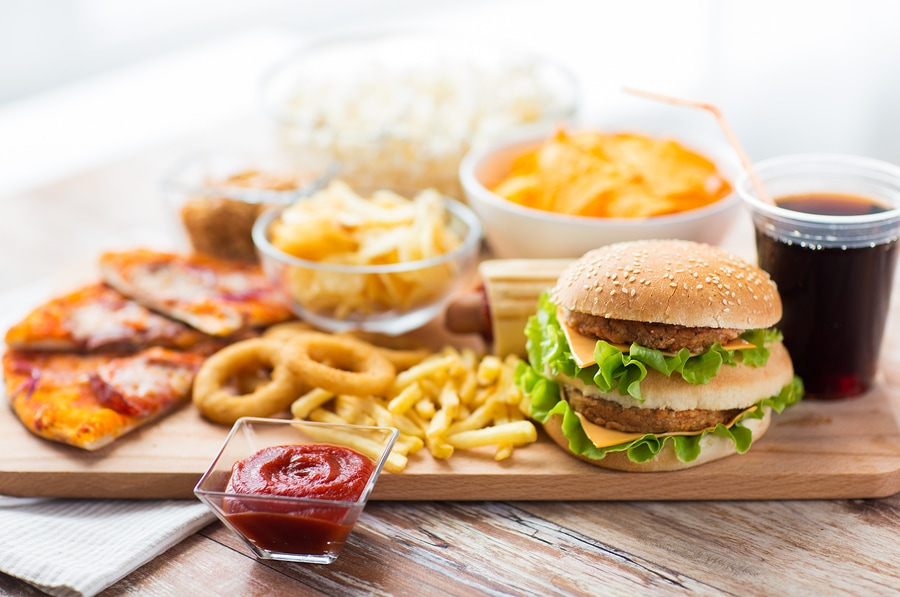 collection of unhealthy fast food on wooden cutting board