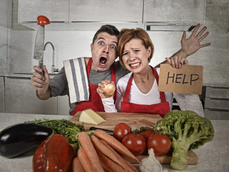 American Couple In Stress At Home Kitchen In Cooking Apron Askin