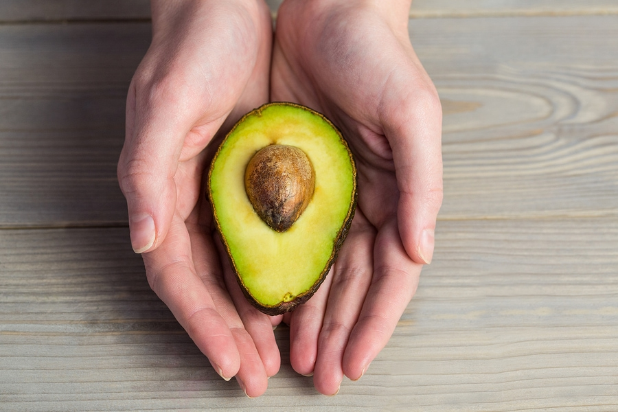 Woman holding sliced avocado with both hands