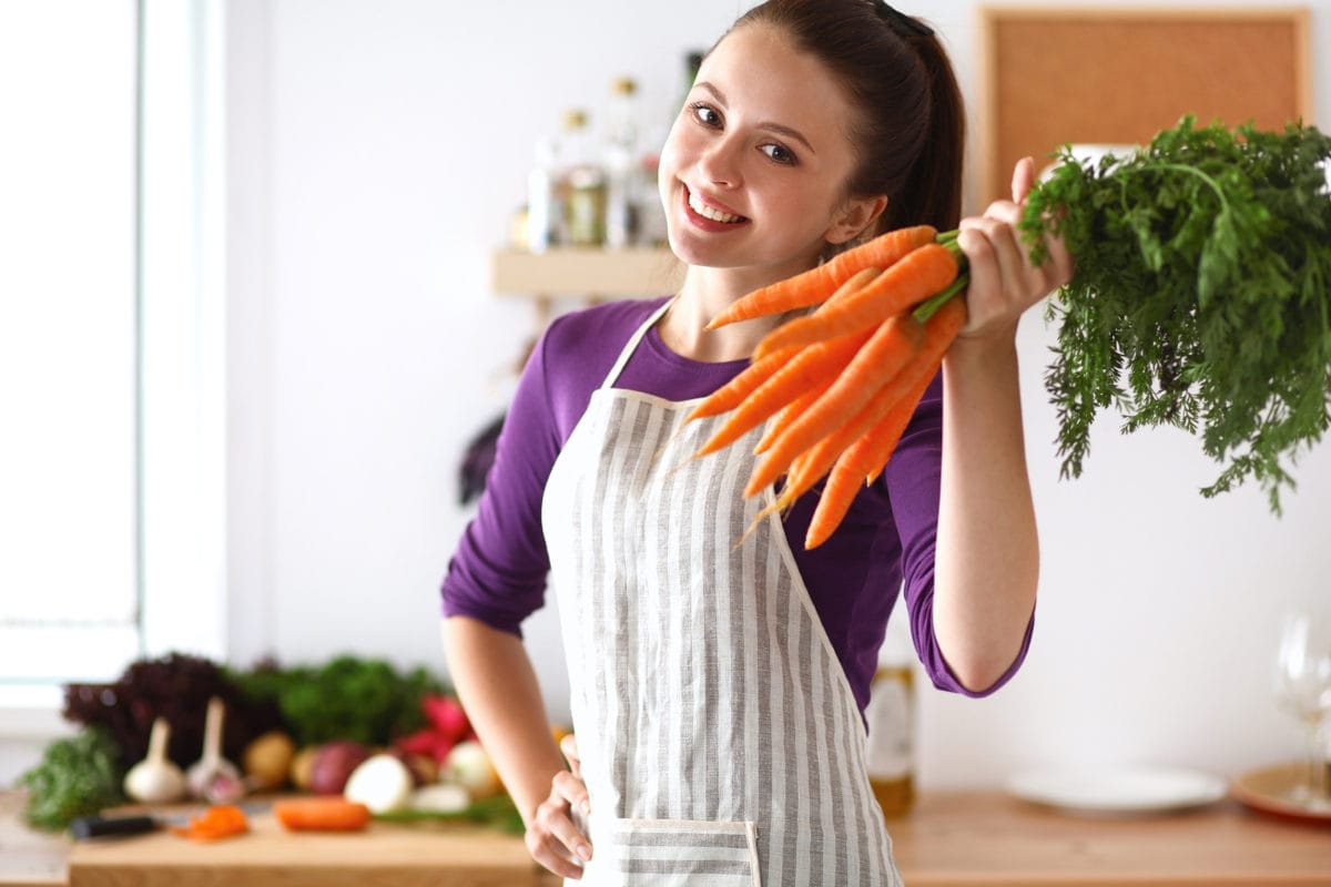 happy young woman holding a carrot bunch in kitchen