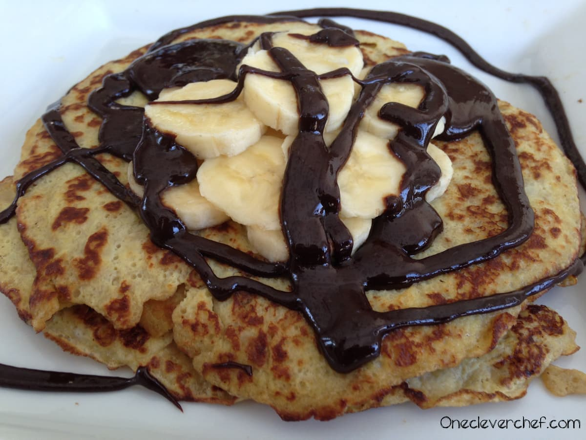 Banana & Egg Pancakes Topped with banans and Homemade Chocolate Syrup | Onecleverchef.com Ingredients: Bananas Eggs, coconut oil, cocoa powder, honey, vanilla. Yum!