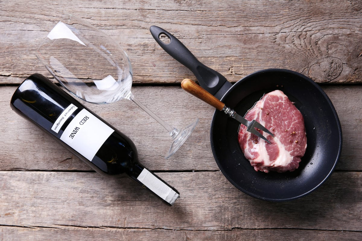 Marbled beef steak and wine bottle on wooden background