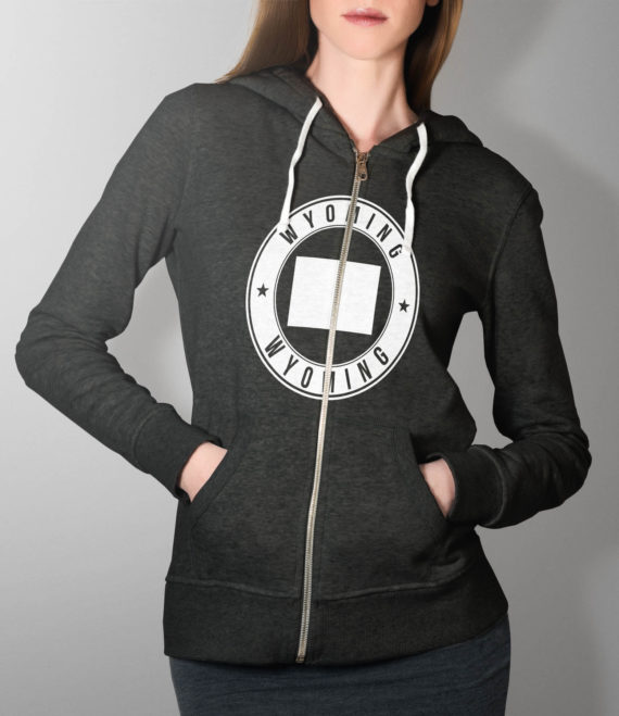 amanda-01-hoody-studio-hands-in-pockets-mockup-dark-heather-grey-wyoming-us-state-emblem-condensed-white