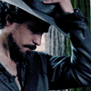 Aramis bowing his head with a hand to his hat.