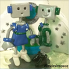 a robot dressed in blue holding hands with a robot dressed in green, text below reads #bridesinspace