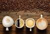 four cups of coffee of various shapes and sizes sitting on a table beside a strew of coffee beans