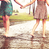 Two girls in dresses walking hand in hand.