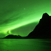 a green aurora arching over a dark mountain.