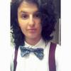 A photograph of me, Panther, in a white social shirt, with a red suspender and a floral bowtie. My hair is dark brown and curly, my eyes are also dark brown and I have a big nose.