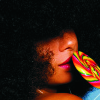 black woman with afro & colorful lollipop