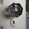 Detail: the glass knob and keyhole of an old door.