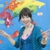 Cheerful woman in front of a colorful map of the world