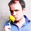 Actor Rory Kinnear sniffing a yellow flower