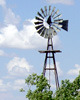 Windmill, trees around base, white clouds behind