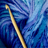 wooden crochet hook on deep blue yarn