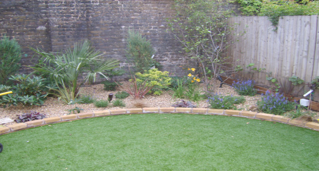 A circular area of lawn tricks the eye as to the width of the garden. As the previous lawn never flourished, and in the interests of low maintenance, we laid artificial turf to make an excellent play surface for the children.