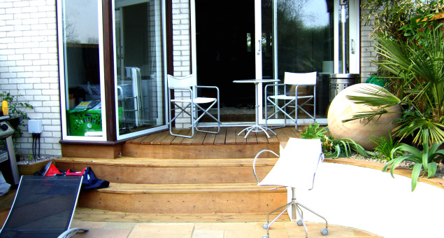 Decking steps were used to link the house to a natural sandstone patio with an attractive nautical star insert. Our clients now had a much larger dining area which was far more practical to use.