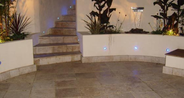 We created a large circular patio area near to the house using elegant cream Travertine stone, surrounded by curved rendered walls with built in hardwood storage benches and dramatic blue LED lighting.