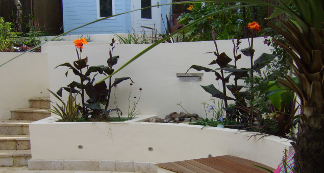Raised beds filled with semi-tropical planting enhance the sense of drama with architectural foliage and vibrant colours.