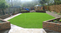 Long thin family garden with play area for children at the end